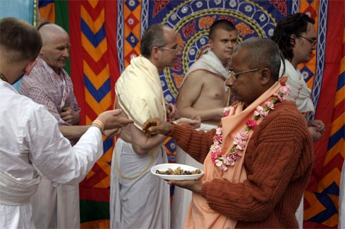 Sripad Bhagavat Maharaj giving out prasadam fruits from fire sacrifice